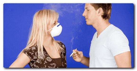мужчина курит около женщины